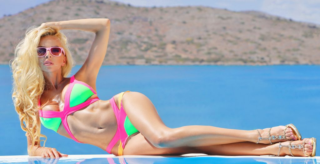 Beautiful woman is standing in sexy swimsuit at swimming pool